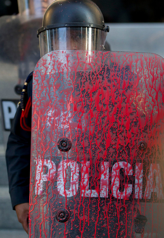 . A police officer\'s shield is covered in red paint that was thrown by protesters marking the anniversary of the Tlatelolco massacre in Mexico City, Wednesday, Oct. 2, 2013. Mexico commemorated the 45th anniversary of the massacre of students holding an anti-government protest, killed by men with guns and soldiers ten days before the 1968 Summer Olympics celebrations in Mexico City. (AP Photo/Eduardo Verdugo)