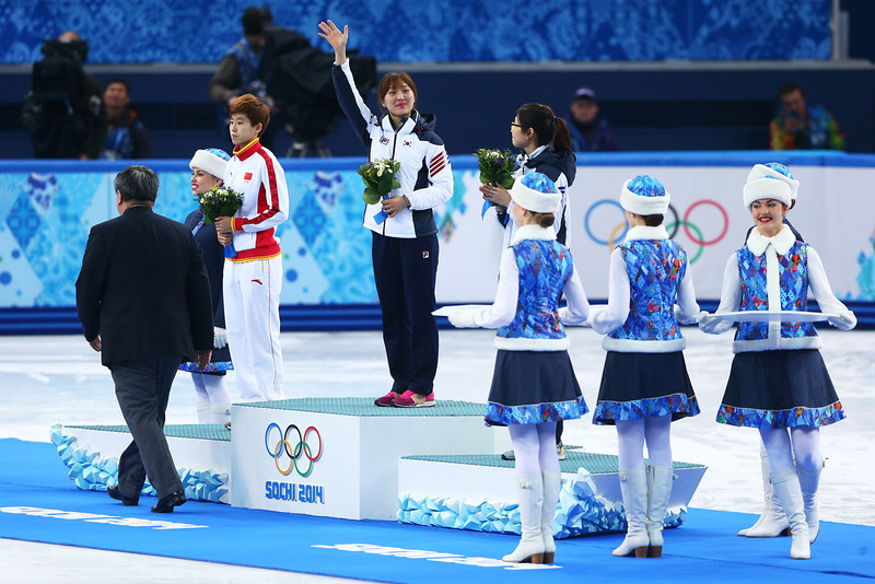 . (L-R) Silver medalist Kexin Fan of China, gold medalist Seung-Hi Park of South Korea and bronze medalist Suk Hee Shim of South Korea celebrate on the podium during the flower ceremony for the Short Track Women\'s 1000m on day fourteen of the 2014 Sochi Winter Olympics at Iceberg Skating Palace on February 21, 2014 in Sochi, Russia.  (Photo by Paul Gilham/Getty Images)