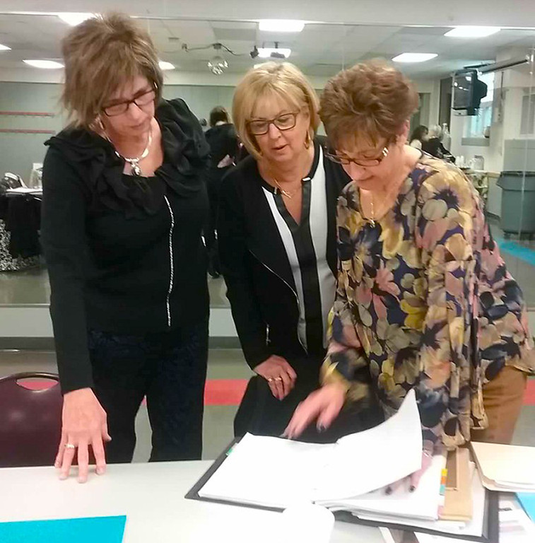 . Dream House design coordinators Kate Weaver, left, Karen Krauss and Kathy Wallace check over design plans at a meeting on March 9 at the Lake County YMCA in Painesville.  {Jean Bonchak For The News-Herald}