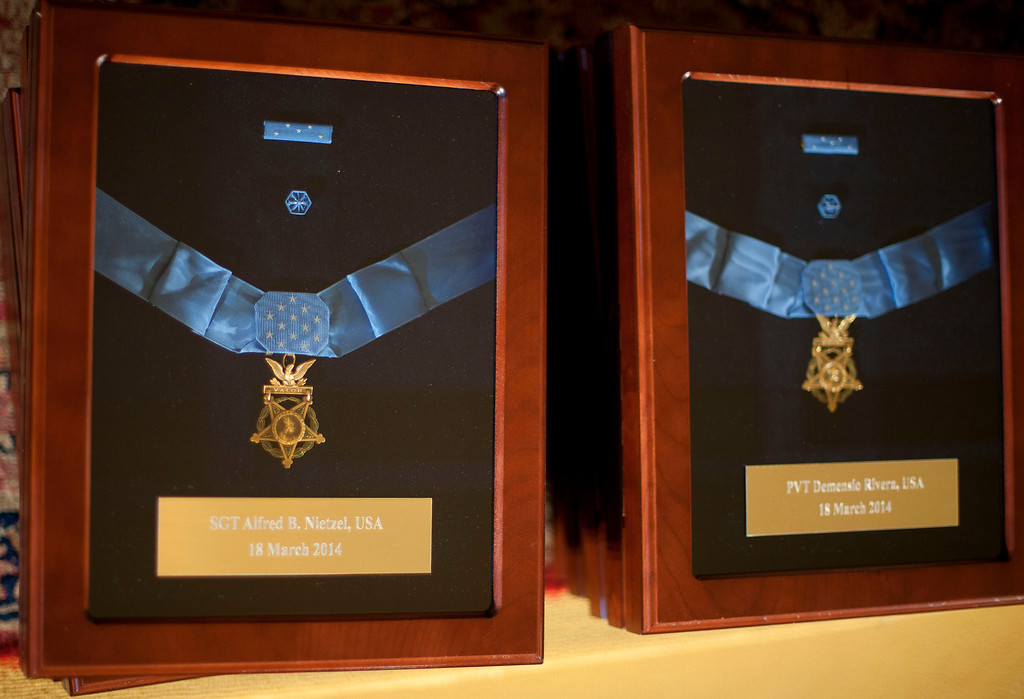. Posthumous Medals of Honor for Sgt. Alfred B. Nietzel, left, and Pvt. Demensio Rivera, are seen in the East Room of the White House in Washington, Tuesday, March 18, 2014, before a ceremony where President Barack Obama will award the medals. The president is moving to right old wrongs by belatedly awarding the Medal of Honor to 24 Army veterans who served during World War II, Korea and Vietnam. (AP Photo/Pablo Martinez Monsivais)