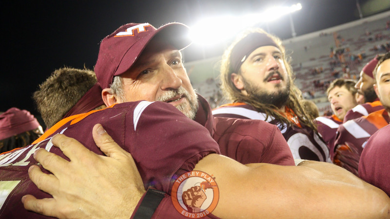 Defensive coordinator Bud Foster, who called the game from the booth for the second week in a row, hugs one his players on the field.The Hokies defeated UVa, 34-31 in overtime. (Mark Umansky/TheKeyPlay.com)
