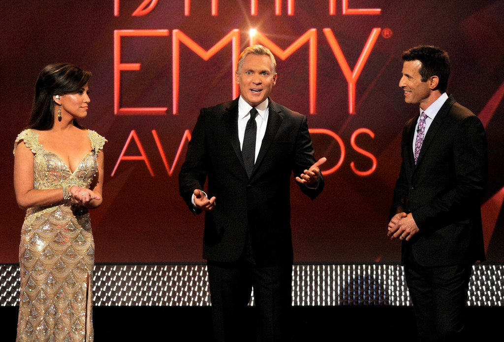 . Hosts, from left, Robin Meade, Sam Champion and AJ Hammer speak on stage at the 40th Annual Daytime Emmy Awards on Sunday, June 16, 2013, in Beverly Hills, Calif. (Photo by Chris Pizzello/Invision/AP)