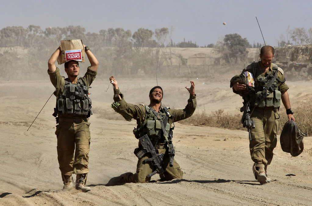 . An Israeli soldier gestures in relief as he walks with comrades near the border between Israel and the Gaza Strip after returning from the Hamas-controlled Palestinian coastal enclave, on August 4, 2014. The Israeli army said today it was resuming its strikes on the Gaza Strip, after the end of a seven-hour humanitarian lull. An army spokesman said troops were redeploying within Gaza while other forces were pulling out in a process which began on August 2. AFP PHOTO/GIL COHEN MAGEN/AFP/Getty Images