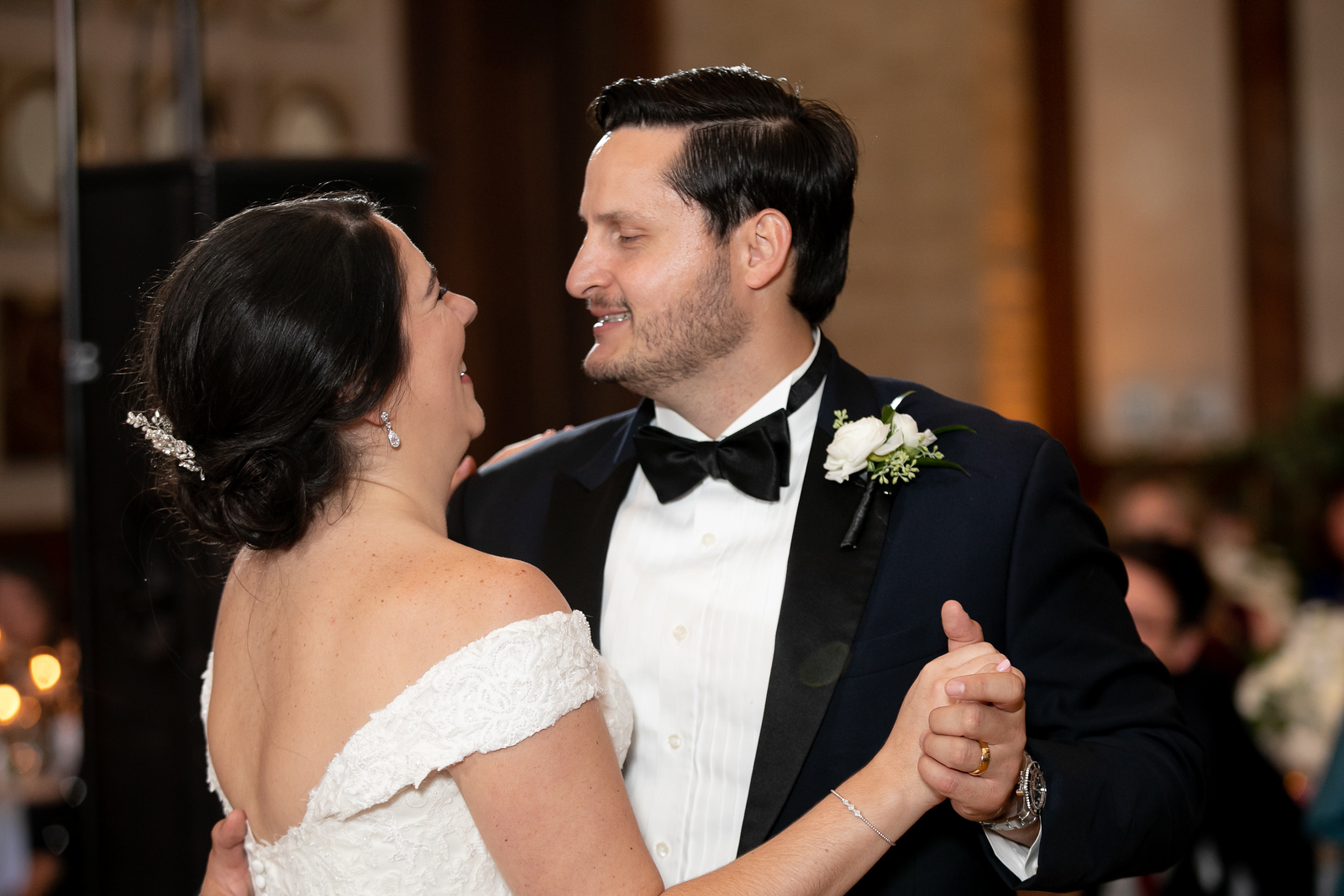 groom smiling at his new bride as she laughs while they dance at their wedding reception