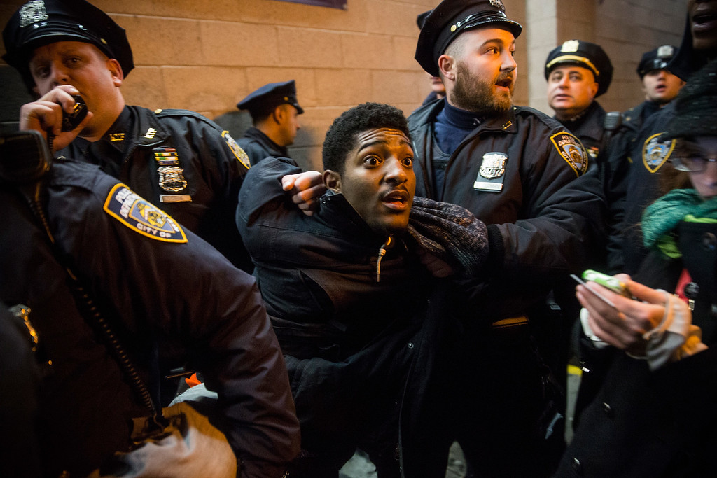 . A demonstrator is arrested inside the Barclays Center subway station after a Brooklyn Nets game while protesting the Staten Island, New York grand jury\'s decision not to indict a police officer involved in the chokehold death of Eric Garner in July on December 8, 2014 in New York City. The royal couple, Prince William and Catherine, Duchess of Cambridge, are on an official three-day visit to New York and were in attendence for the Brooklyn Nets game. (Photo by Andrew Burton/Getty Images)