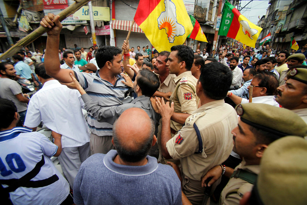 . Indian policemen restrain Hindus protesting against the state government after rival communities clashed in Kishtwar, in Jammu, India, Saturday, Aug. 10, 2013. Indian forces fired warning shots Saturday to enforce a curfew and to push angry people back into their homes in Kishtwar, in the Indian portion of Kashmir where clashes between Muslims and Hindus during Eid celebrations killed at least two people and injured another 24. (AP Photo/Channi Anand)