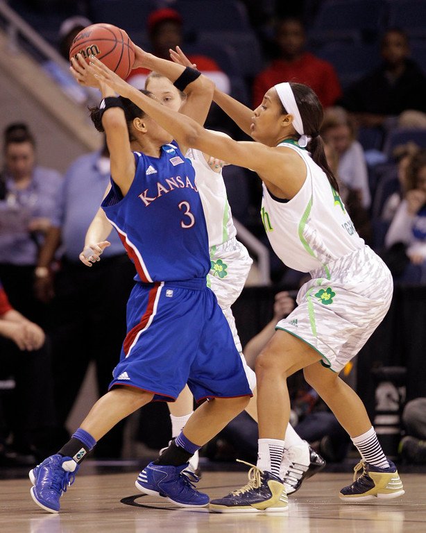 . Notre Dame guard Skylar Diggins, right, pressures Kansas guard Angel Goodrich (3) during a regional semi-final of the NCAA college basketball tournament  Sunday, March 31,2013, in Norfolk, Va.  Notre Dame won 93-63. (AP Photo/Steve Helber)