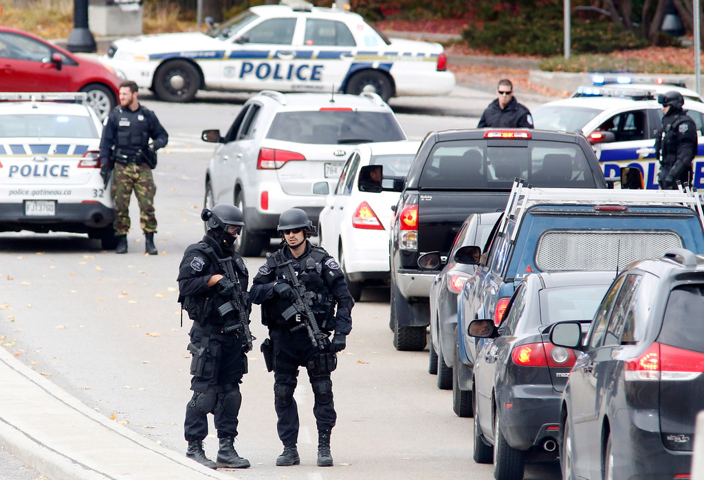 . Police search cars and pedestrians as they leave the Alexandra Bridge and enter Gatineau, Quebec near the Parliament Buildings  in Ottawa  on Wednesday, Oct. 22, 2014.   (AP Photo/The Canadian Press, Patrick Doyle)