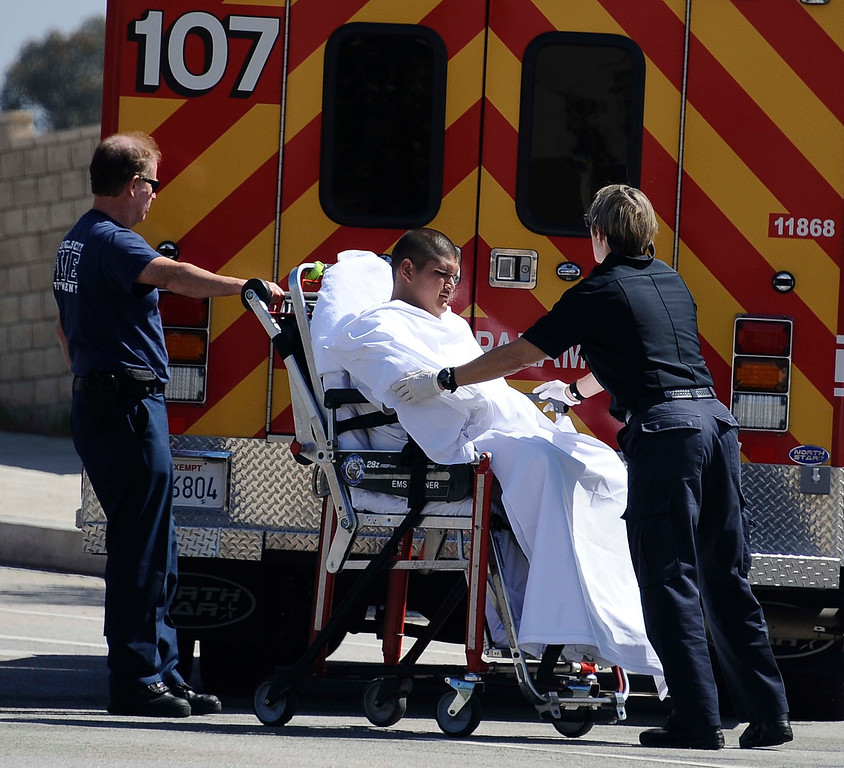 . LA city fire paramedics transport one of the surviving victims who fled the scene and was brought back to the crash site, after a car crashed into a traffic light pole and burst into flames Friday morning in Porter Ranch, burning one person to death and critically injuring the driver who died later at the hospital and another who escaped from the car The crash on Rinaldi Street near Mason Avenue happened just after 10 a.m. No other vehicles appeared to be involved in the crash. The car was going at a high rate of speed down Rinaldi St. and swerved  to miss another car that was going slower and lost control and hit the traffic light poll and burst into flames. Porter Ranch California, March 29,2013 PHOTO BY Gene Blevins/LA DailyNews