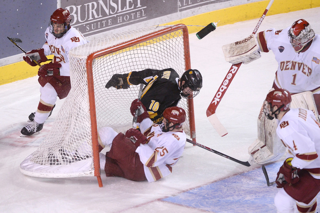 . DENVER, CO. - FEBRUARY 21, 2014: Denver center Matt Tabrum (25) and Colorado College center Cody Bradley (10) crashed into the net in the second period. The University of Denver hockey team hosted Colorado College at Magness Arena Friday night, February 21, 2014. Photo By Karl Gehring/The Denver Post