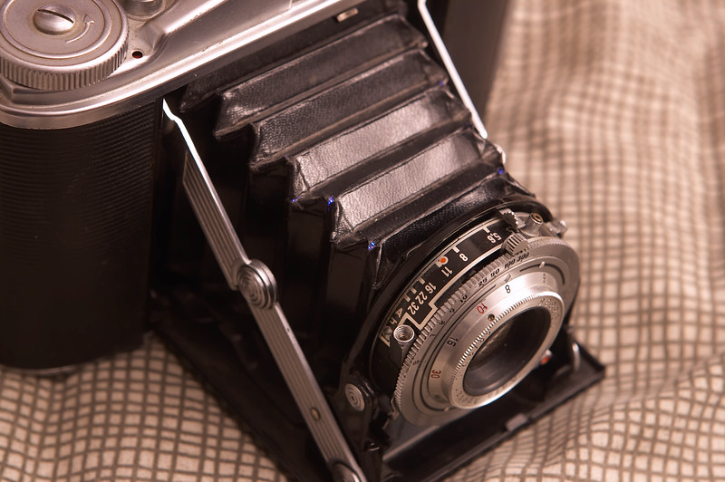 Sadly, the 50-year-old bellows has several pinhole light leaks (Blue LED flashlight inside camera)