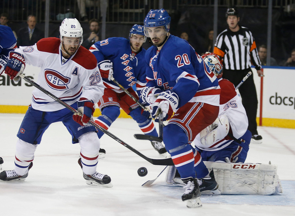 . Montreal Canadiens defenseman Josh Gorges (26) watches as New York Rangers left wing Chris Kreider (20) looks at a loose puck in front of Canadiens goalie Dustin Tokarski (35) during the second period of Game 3 of the NHL hockey Stanley Cup playoffs Eastern Conference finals, Thursday, May 22, 2014, in New York. (AP Photo/Kathy Willens)
