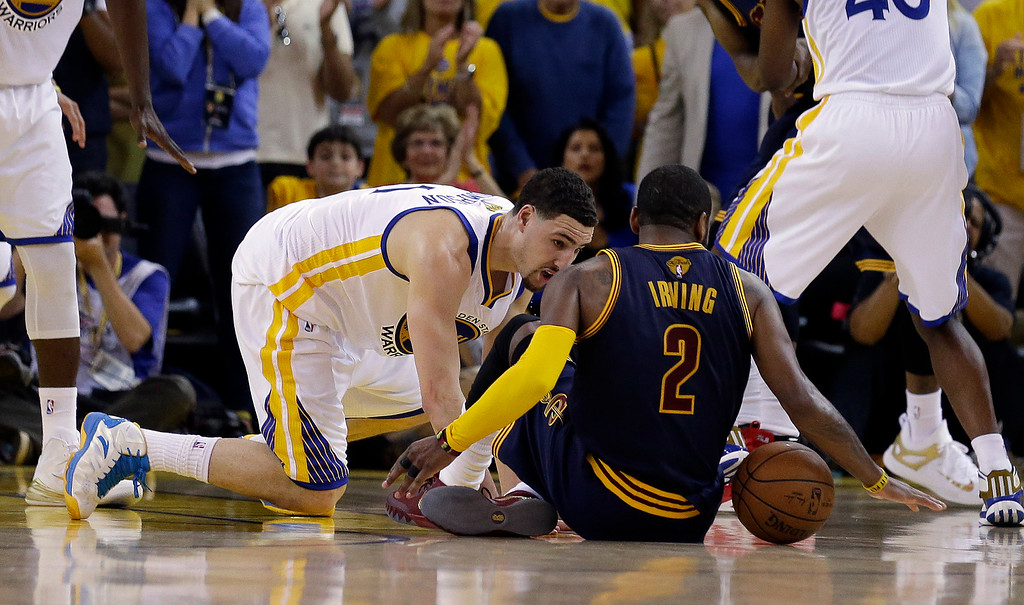 . Cleveland Cavaliers guard Kyrie Irving (2) tries to control the ball next to Golden State Warriors guard Klay Thompson during overtime of Game 1 of basketball\'s NBA Finals in Oakland, Calif., Thursday, June 4, 2015. Irving left the game with an injury right after this play. (AP Photo/Ben Margot)