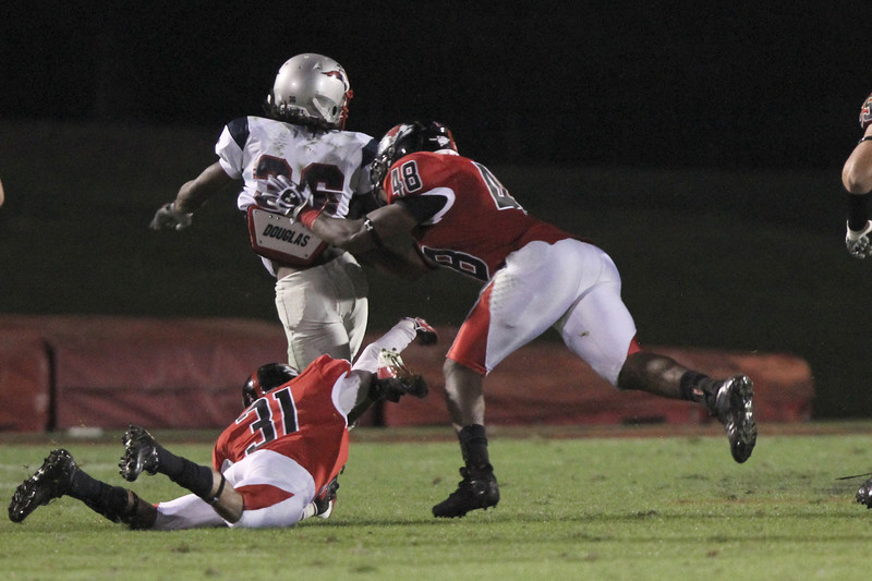 Keon Williams (31) and Azizz Higgins (48) reach to pull MNU's player down for a tackle