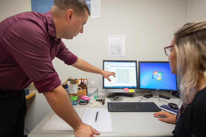 SQL Coordinator Bryan Gillis (left), and Library Specialist II Shelby Gonzalez examine archived maps in the Mary and Jeff Bell Library collections.