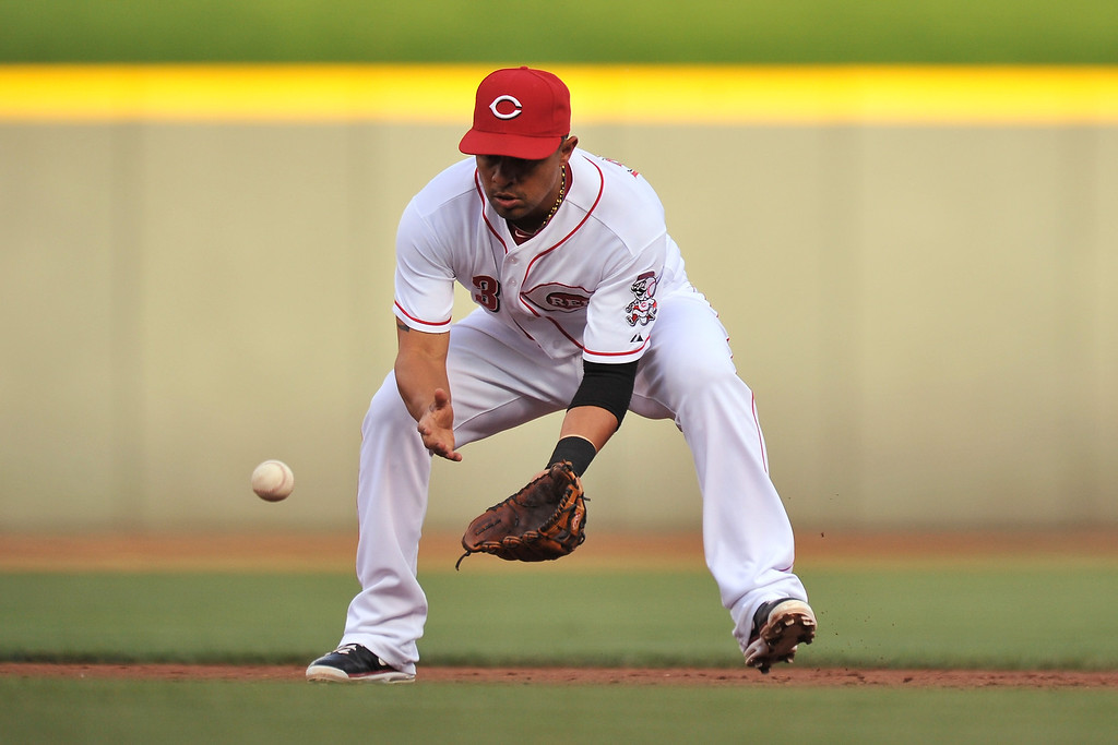 . Cesar Izturis #3 of the Cincinnati Reds fields a ground ball against the Colorado Rockies in the second inning at Great American Ball Park on June 4, 2013 in Cincinnati, Ohio. Colorado defeated Cincinnati 5-4.  (Photo by Jamie Sabau/Getty Images)