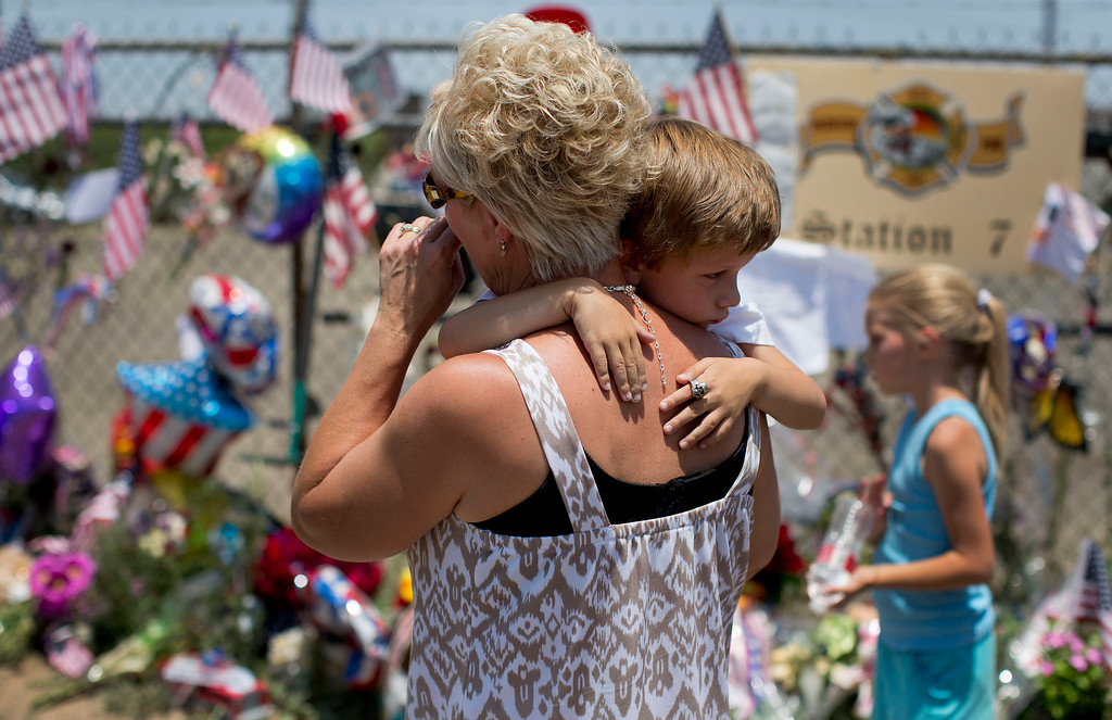 . Lynn Paupore walks along the makeshift memorial with her grandson Bradley Richtig, 5, and granddaughter Kylie Richtig, 8, outside the Granite Mountain Interagency Hotshot Crew fire station, Wednesday, July 3, 2013 in Prescott, Ariz. A mile-high city about 90 miles northwest of Phoenix, Prescott remains a modern-day outpost of the pioneer spirit. It\'s that spirit that will guide officials as they navigate the days ahead and figure out how to honor the elite Hotshot firefighters who died Sunday in a nearby wind-driven wildfire that is still burning. (AP Photo/Julie Jacobson)
