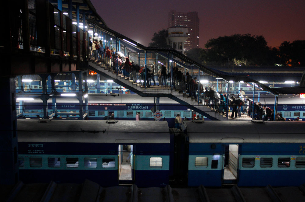 Description of . Passengers walk as trains wait to run at a train station in New Delhi, India,  Wednesday, Jan. 9, 2013. (AP Photo/Tsering Topgyal)
