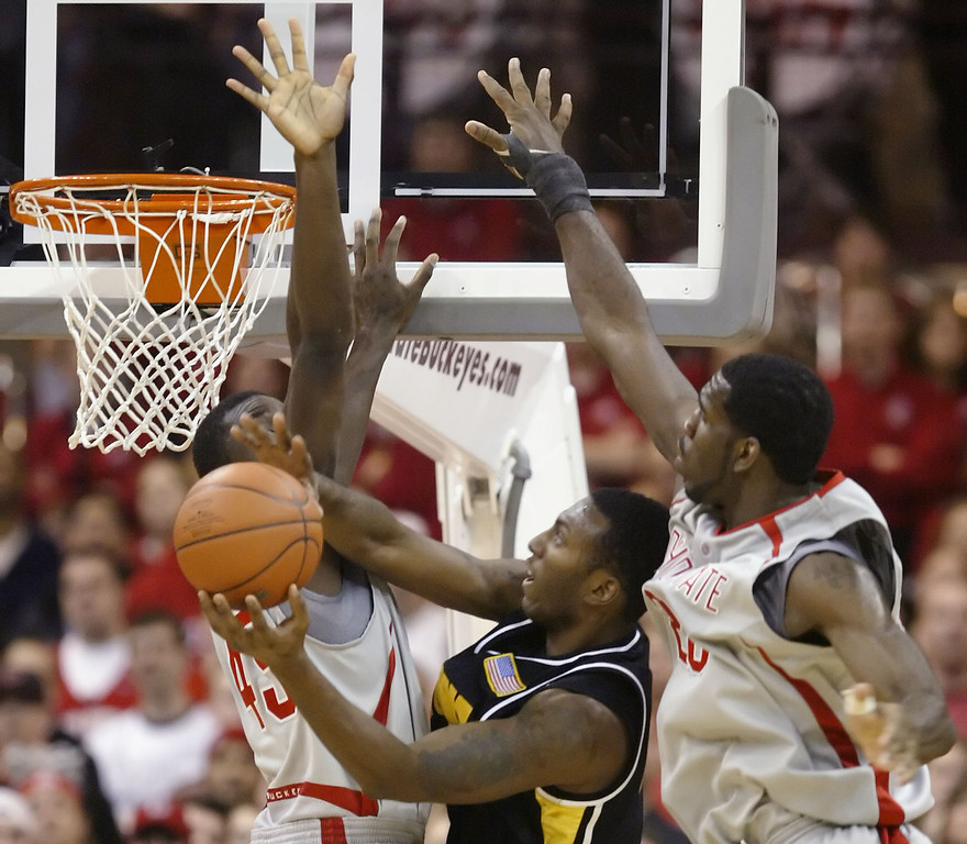 . Iowa\'s Cyrus Tate, center, tries to take a shot between Ohio State\'s Othello Hunter, left, and Greg Oden during the second half of an NCAA basketball game Saturday, Jan. 20, 2007, in Columbus, Ohio. Ohio State beat Iowa, 82-63. (AP Photo/Jay LaPrete)