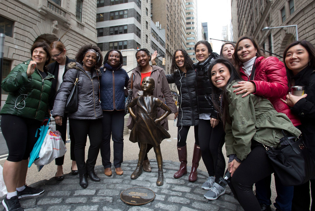 ". A group of women stop to pose with a statue of a fearless girl, Wednesday, March 8, 2017, in New York. The statue was installed by an investment firm in honor of International Women\'s Day. An inscription at the base reads, ""Know the power of women in leadership. She makes a difference. State Street Global Advisors.\"" (AP Photo/Mark Lennihan)"