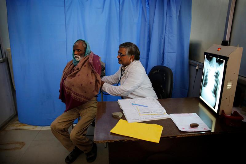 . In this Monday, Feb. 3, 2014 photo, senior chest physician Dr. A.K. Upadhaya, right, checks patient Shyam Lal, suspected to have tuberculosis, at Lal Bahadur Shastri Government Hospital in Ram Nagar, Varanasi, India. (AP Photo/Rajesh Kumar Singh)