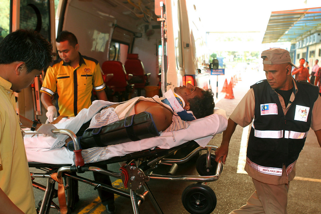 . An injured passenger is carried on a stretcher on the arrival at a hospital in Kuala Lumpur after a bus carrying tourists and local residents fell into a ravine near the Genting Highlands, about an hour\'s drive from Kuala Lumpur, Malaysia, Wednesday, Aug. 21, 2013. (AP Photo) MALAYSIA OUT