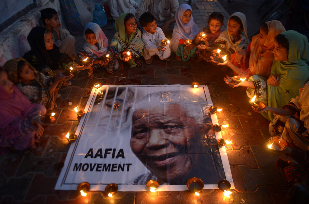 . Pakistani schoolchildren hold lamps during a memorial tribute to South African late president Nelson Mandela, in Karachi on December 6, 2013. People gathered in cities around the world to make their own personal tributes to Nelson Mandela on December 6, leaving flowers and setting up makeshift shrines in an outpouring of emotion for South Africa\'s anti-apartheid icon. AFP PHOTO/RIZWAN TABASSUM/AFP/Getty Images