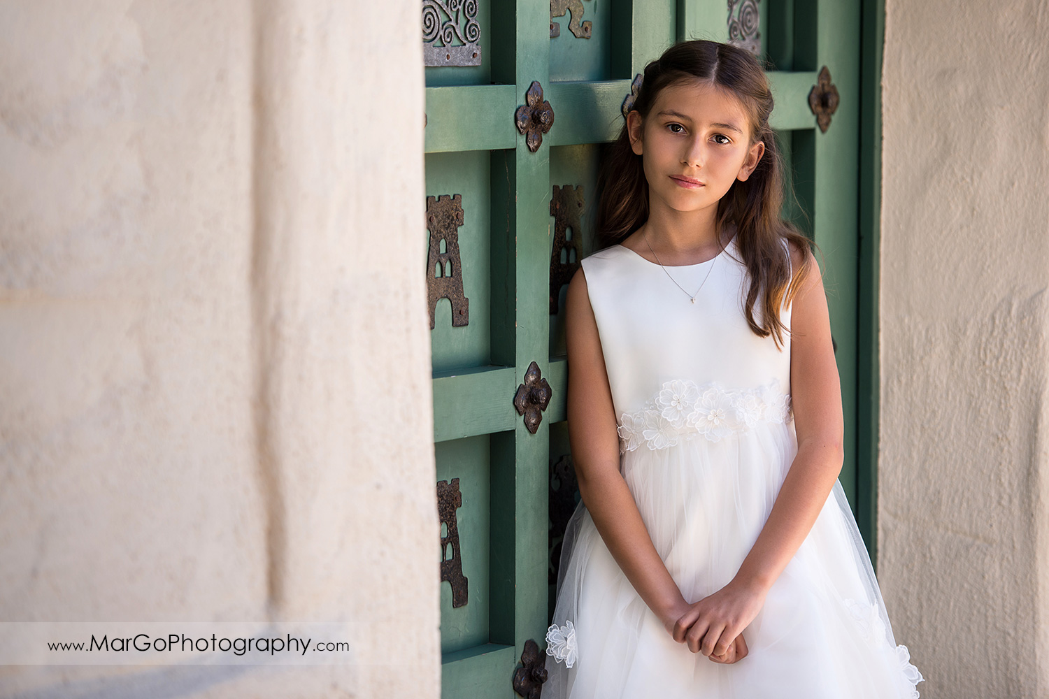 portrait of first communion girl in white dress in front of green door at Cafe Wisteria in Menlo Park