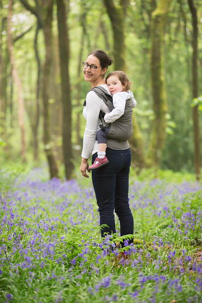 Izmi_Toddler_Carrier_Cotton_Mid_Grey_Lifestyle_Back_Carry_Mum_Smiling_In_Field.jpg