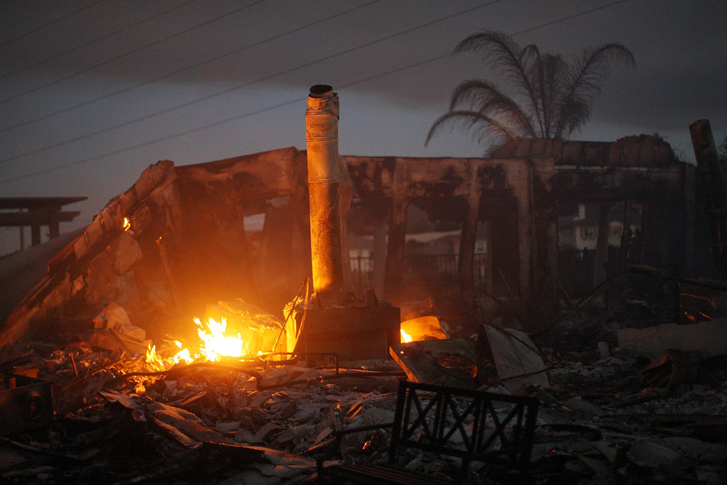 . The ruins of a home smolder in the night after it was destroyed in the Poinsettia fire, one of nine wildfires fueled by wind and record temperatures that erupted in San Diego County throughout the day, on May 14, 2014 in Carlsbad, California.   (Photo by David McNew/Getty Images)