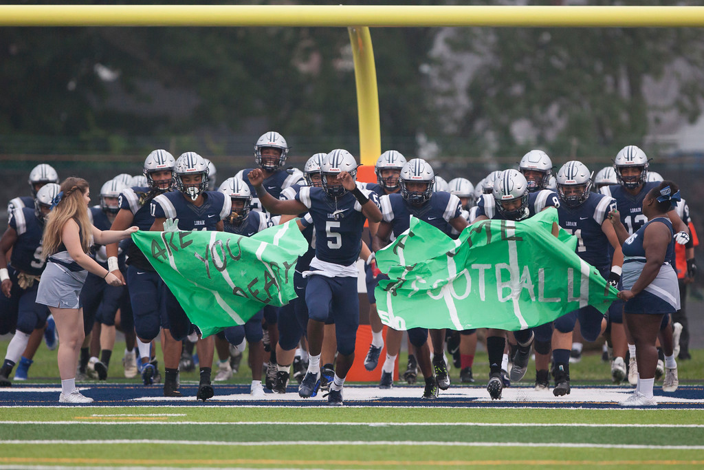 . Jen Forbus - The Morning Journal<br> Lorain quarterback Jordan Jackson leads his squad onto the field for their game against Ottawa St. Joseph on Sept. 14.