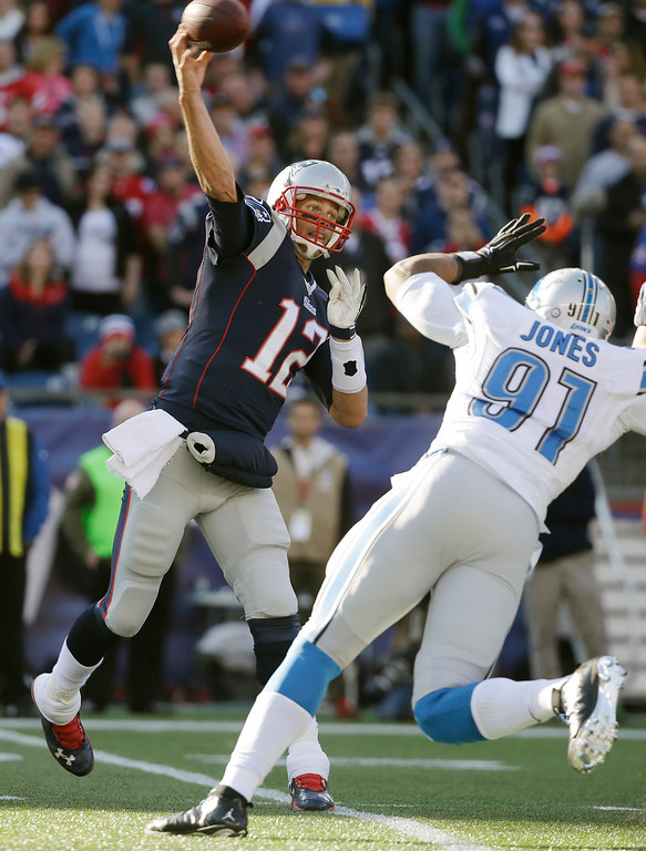 . New England Patriots quarterback Tom Brady (12) passes against the rush by Detroit Lions defensive end Jason Jones (91) in the first half of an NFL football game Sunday, Nov. 23, 2014, in Foxborough, Mass. (AP Photo/Steven Senne)