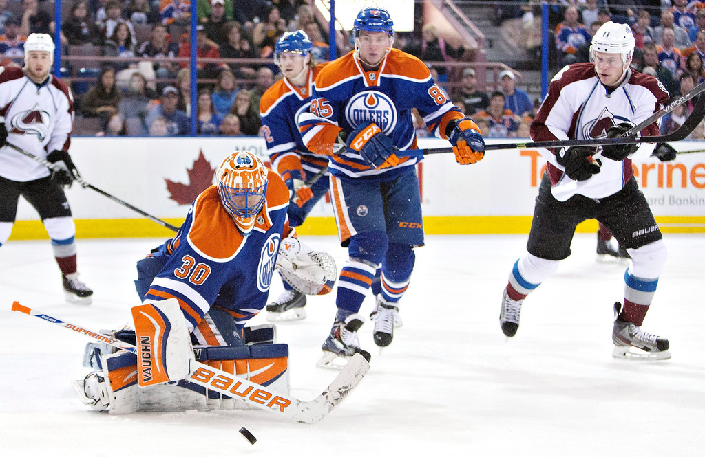 . Colorado Avalanche\'s Jamie McGinn (11) and Edmonton Oilers\' Jeff Petry (2) and Martin Marincin (85) chase the rebound as goalie Ben Scrivens (30) makes the save during first period NHL hockey action in Edmonton, Alberta, on Tuesday April 8, 2014. (AP Photo/The Canadian Press, Jason Franson)