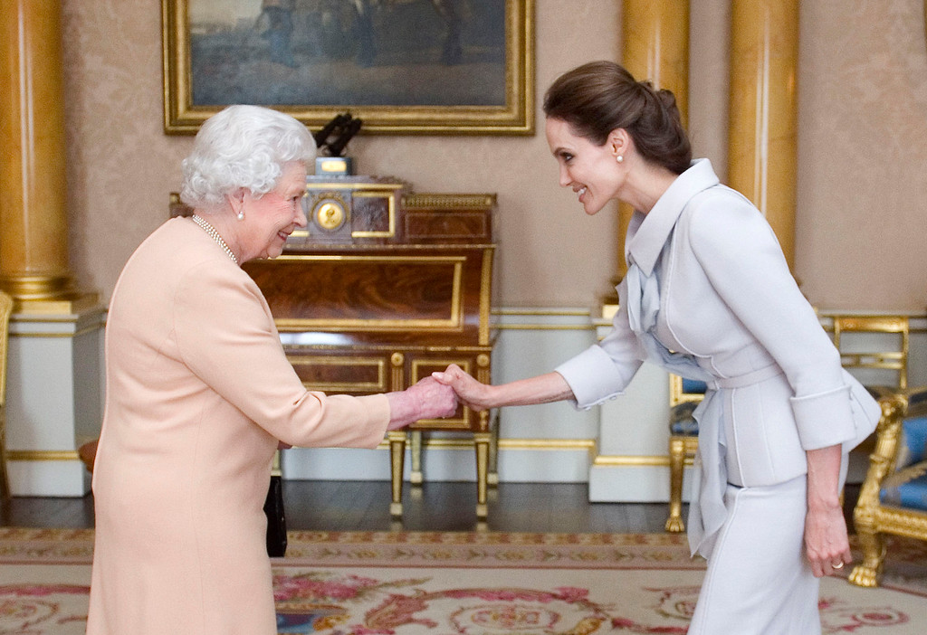 . U.S actress Angelina Jolie, right, is presented with the Insignia of an Honorary Dame Grand Cross of the Most Distinguished Order of St Michael and St George by Britain\'s Queen Elizabeth II at Buckingham Palace, London, Friday, Oct. 10, 2014.  (AP Photo/Anthony Devlin, pool)