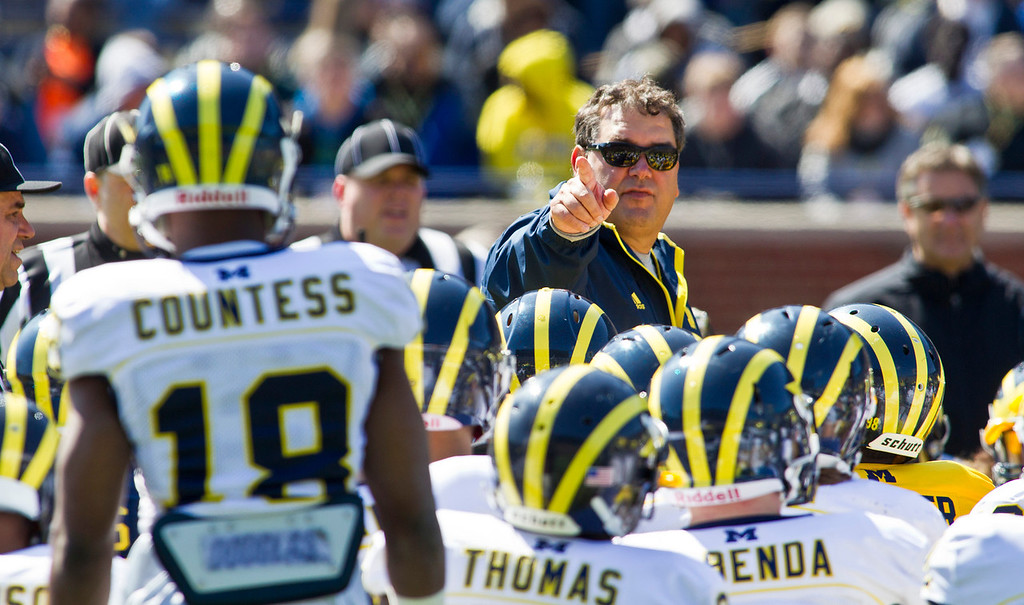 . Michigan head coach Brady Hoke, center top, addresses his players gathered around him during the football team\'s annual spring game, Saturday, April 5, 2014, in Ann Arbor, Mich. (AP Photo/Tony Ding)