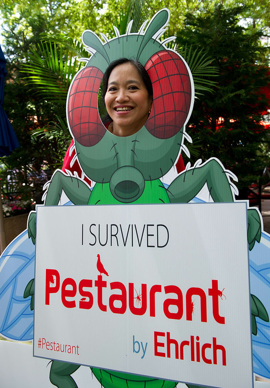 . A patron has her photo taken with a cardboard insect cutout after eating insects June 4, 2014 during a global Pestaurant event sponsored by Ehrlich Pest Control, held at the Occidental Restaurant in Washington, DC. For one day only, pop-up Pestaurants will appear in cities across the globe to offer sweet and savory edible insects, grasshopper burgers and much more. Ehrlich Pest Control will be donating $5 USD to DC Central Kitchen for every person who eats something at the event.  (KAREN BLEIER/AFP/Getty Images)