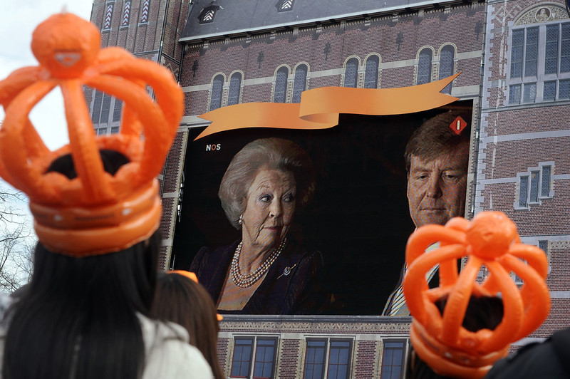 . Two girls wearing orange plastic crowns watch King Willem Alexander and Queen Beatrix broadcastt on giant screen at the Dam square during the Queen\'s abdication ceremony in Amsterdam, The Netherlands, 30 April 2013. Dutch Crown Prince Willem-Alexander became Europe\'s youngest monarch on Tuesday after his mother, Queen Beatrix, abdicated and his country hailed the avowedly 21st-century king with a massive, orange-hued party.  EVERT ELZINGA/AFP/Getty Images