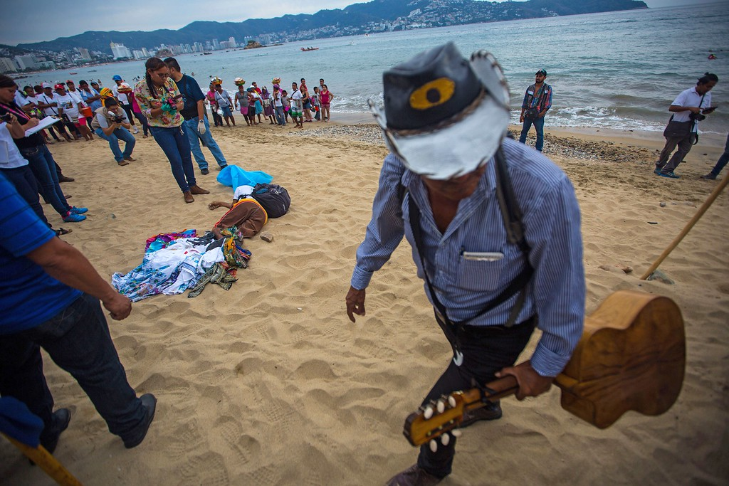 . A musician walks past forensic workers as they surround the body of a murdered man at Hornos beach, in the tourist city of Acapulco, Guerrero state, Mexico on January 29, 2016. Guerrero is one of Mexico\'s poorest and most violent states, where a lucrative drug trade has flourished. PEDRO PARDO/AFP/Getty Images