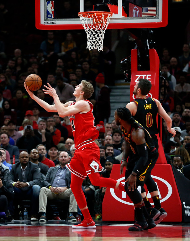 . Chicago Bulls\' Lauri Markkanen, left, scores on a reverse layup past Cleveland Cavaliers\' Kevin Love (0) and Jae Crowder during the first half of an NBA basketball game Monday, Dec. 4, 2017, in Chicago. (AP Photo/Charles Rex Arbogast)
