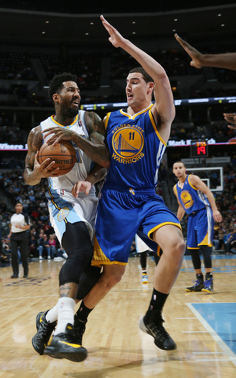 . Denver Nuggets forward Wilson Chandler, left, is stopped as he drives for a shot by Golden State Warriors guard Klay Thompson in the third quarter of the Warriors\' 89-81 victory in an NBA basketball game in Denver on Monday, Dec. 23, 2013. (AP Photo/David Zalubowski)