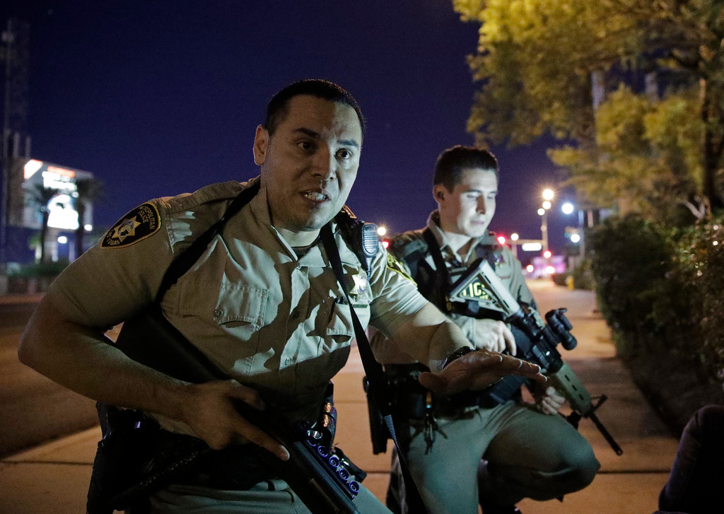 . Police officers advise people to take cover near the scene of a shooting near the Mandalay Bay resort and casino on the Las Vegas Strip, Sunday, Oct. 1, 2017, in Las Vegas. (AP Photo/John Locher)