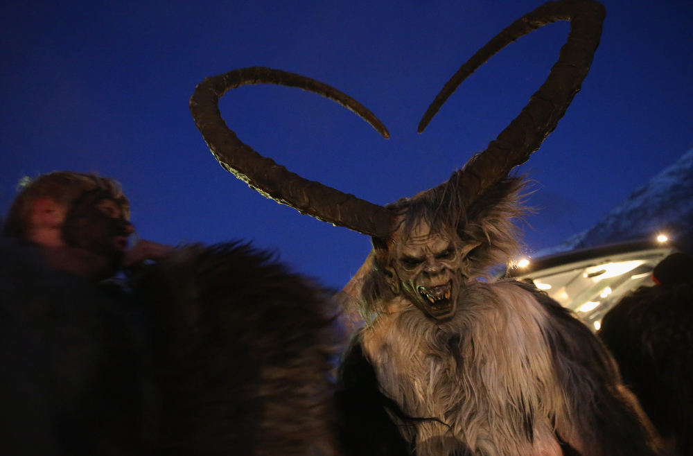 . A participant who arrived by bus tries on his Krampus creature mask as other participants put on their costumes prior to Krampus night on November 30, 2013 in Neustift im Stubaital, Austria. Sixteen Krampus groups including over 200 Krampuses participated in the first annual Neustift event. Krampus, in Tyrol also called Tuifl, is a demon-like creature represented by a fearsome, hand-carved wooden mask with animal horns, a suit made from sheep or goat skin and large cow bells attached to the waist that the wearer rings by running or shaking his hips up and down. Krampus has been a part of Central European, alpine folklore going back at least a millennium, and since the 17th-century Krampus traditionally accompanies St. Nicholas and angels on the evening of December 5 to visit households to reward children that have been good while reprimanding those who have not. However, in the last few decades Tyrol in particular has seen the founding of numerous village Krampus associations with up to 100 members each and who parade without St. Nicholas at Krampus events throughout November and early December.  (Photo by Sean Gallup/Getty Images)