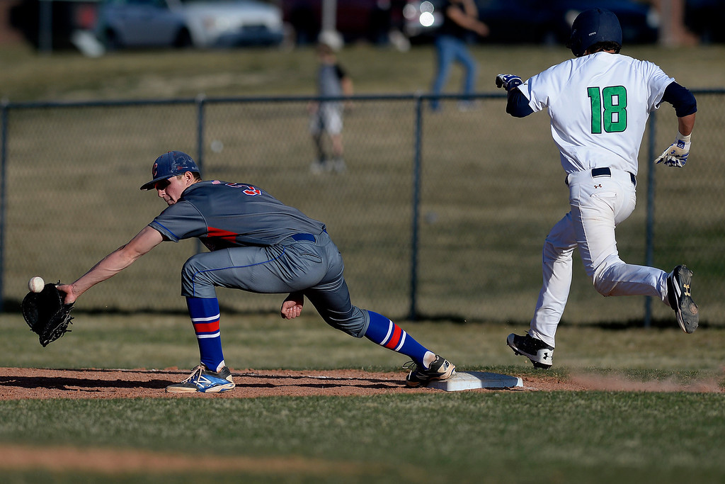 . Aurora, CO - APRIL 08: Jack Gillett (5) of the Cherry Creek Bruins cannot handle the ball thrown by Jack Hallmark (11) as Joseph Sanchez (18) of the Overland Trailblazers makes it aboard safely in the bottom of the seventh inning. Overland hosted Cherry Creek on Tuesday, April 8, 2014. (Photo by AAron Ontiveroz/The Denver Post)