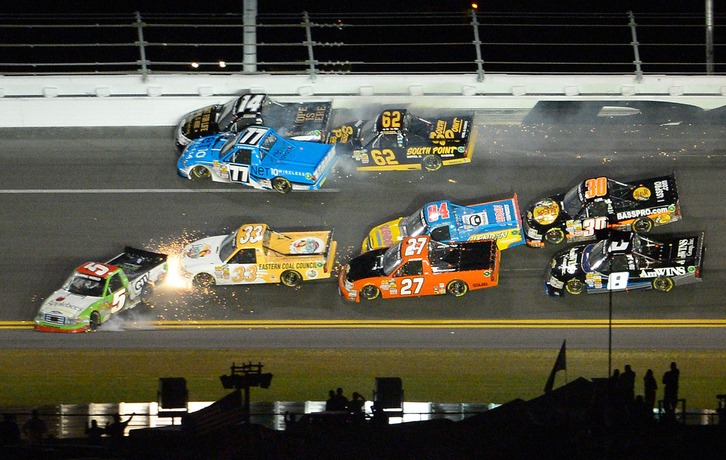 . A wreck between Turns 3 and 4 ensnares Tim George Jr. (5), John King (33), Jeff Agnew (27), Chris Fontaine (84), Brennan Newberry (14), German Quiroga (77), Brendan Gaughan (62), Ryan Truex (30), and Max Gresham (8) on Lap 53 during the NASCAR Truck Series auto race at Daytona International Speedway in Daytona Beach, Fla., Friday, Feb. 22, 2013. (AP Photo/Phelan M. Ebenhack)