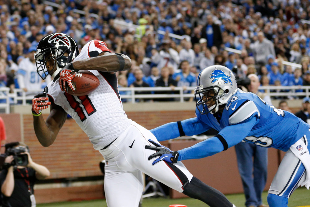 Description of . Atlanta Falcons wide receiver Julio Jones (11) falls into the end zone on a 16-yard touchdown as Detroit Lions cornerback Chris Houston defends during the second quarter of an NFL football game at Ford Field in Detroit, Saturday, Dec. 22, 2012. (AP Photo/Rick Osentoski)
