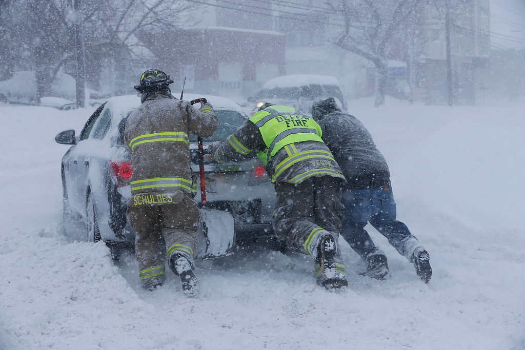 . Firefighters from West End Hose Company in Depew, N.Y. help a stuck motorist on Transit Road, Tuesday, Nov. 18, 2014.  Several feet of lake-effect snow paralyzed the Buffalo area Tuesday, forcing state troopers to deliver blankets and other supplies to motorists stranded on the New York State Thruway and adding an ominous note to a wintry season that\'s already snarling travel and numbing fingers from the Midwest to the Carolinas.  (AP Photo/The Buffalo News, Derek Gee)