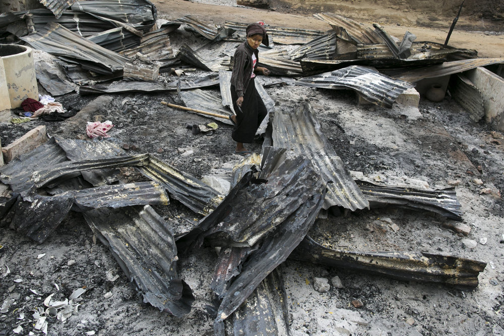 . Burmese woman looks for anything to salvage among debris left by a fire on April 5, 2013 in Meiktila, Myanmar.  Recent sectarian violence between Buddhists and Muslims in March left 43 people dead, with large areas of the town completely destroyed by fires and looting, while many were injured with thousands of Muslims now homeless. Many Muslims who had money fled as the violence after began to spin out of control while the remaining people are being kept in well policed IDP camps in the town.  (Photo by Paula Bronstein/Getty Images)