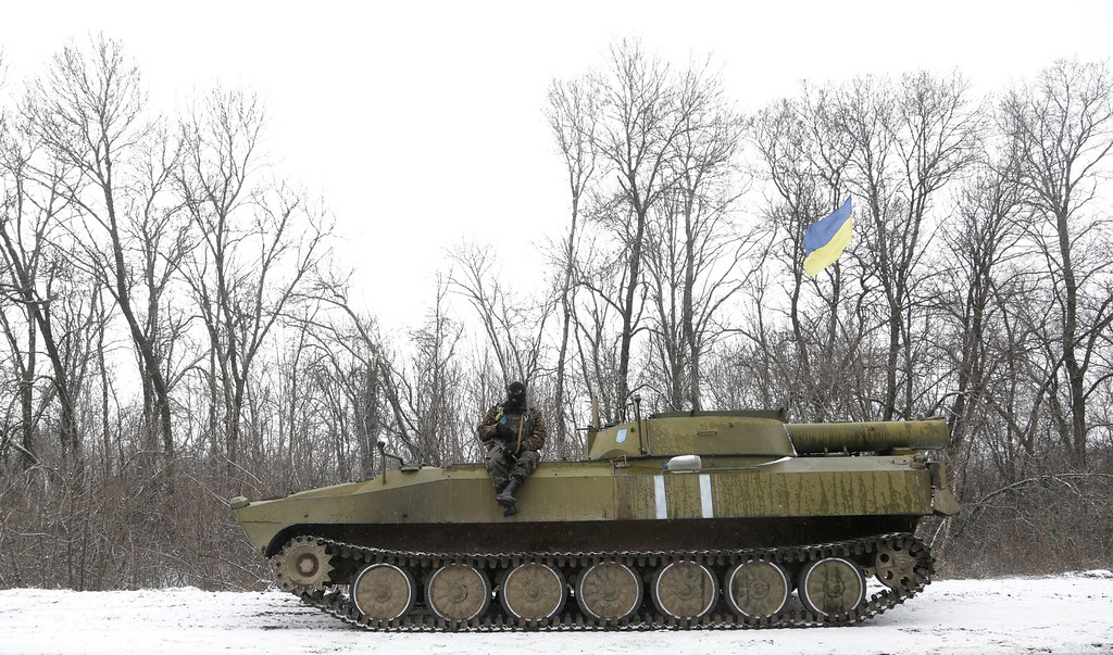 . An Ukrainian soldier rests on his vehicle near the road between the towns of Debaltseve and Artemivsk, Ukraine, Monday, Feb. 16, 2015. The Ukrainian government and Russia-backed rebels accused each other Monday of violating a cease-fire in eastern Ukraine, a day before the parties are due to start withdrawing heavy weaponry under a recently brokered deal. The cease-fire, which went into effect on Sunday, had raised cautious hopes for an end to the 10-month-old conflict, which has already claimed more than 5,300 lives. (AP Photo/Petr David Josek)