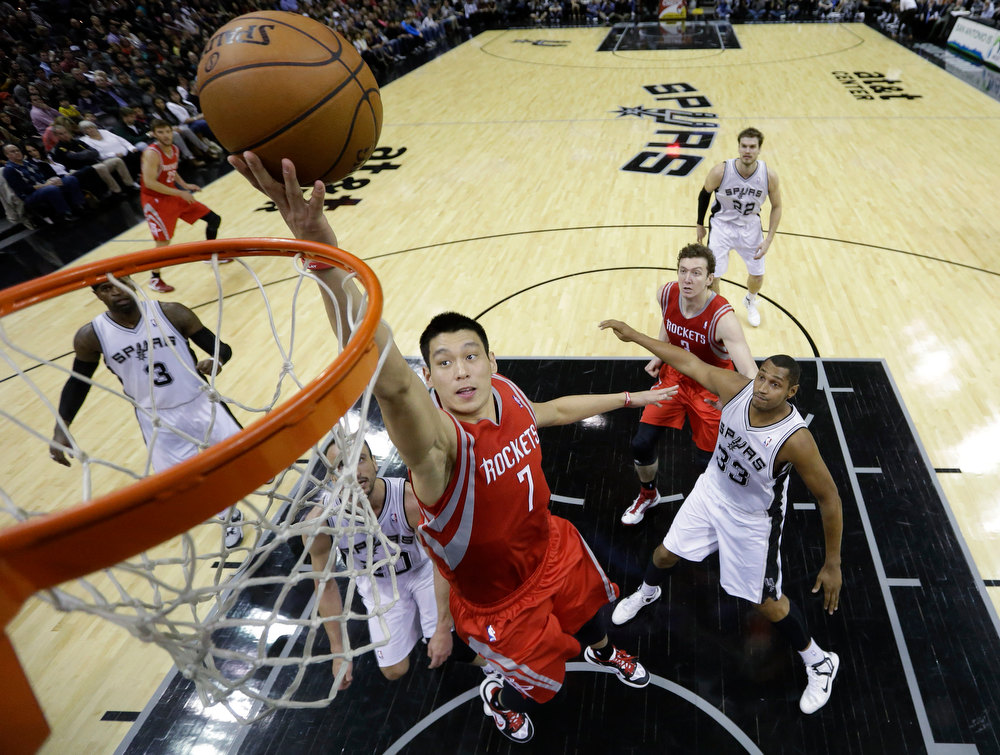 Description of . Houston Rockets' Jeremy Lin (7) scores as San Antonio Spurs Stephen Jackson (3),  Manu Ginobili, center, of Argentina, and Boris Diaw (33) look on during the second quarter of an NBA basketball game, Friday, Dec. 28, 2012, in San Antonio. Jeremy Lin ranked as Google's seventh most searched trending person of 2012. (AP Photo/Eric Gay)