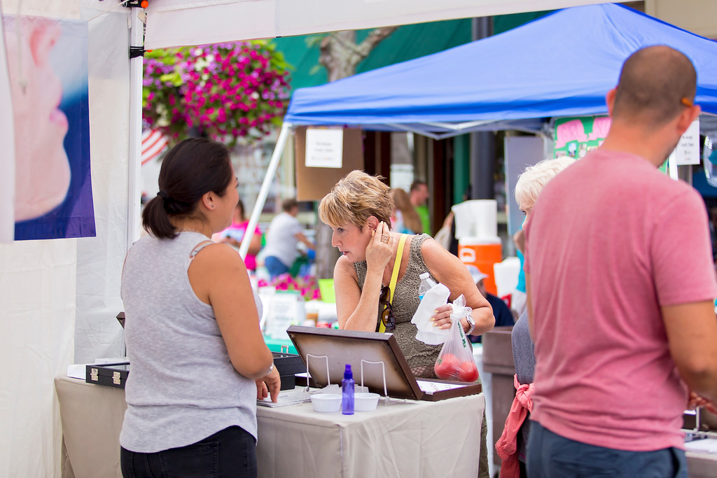 . Gayle Sikula checks out the craft of a vendor at the 2017 Willoughby ArtsFest. The event returns to downtown Willoughby on July 21. For mroe information, visit willoughbyartsfest.com. (Carrie Garland � The News-Herald)